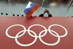 A Russian skating fan holds the country's national flag over the Olympic rings before the start of the men's 10,000-meter speedskating race at Adler Arena Skating Center during the 2014 Winter Olympics in Sochi, Russia, Tuesday, Feb. 18, 2014.(AP Photo/David J. Phillip )