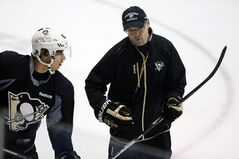 Pittsburgh Penguins head coach Dan Bylsma, right, talks with captain Sidney Crosby during an NHL hockey practice in Canonsburg, Pa., Sunday, Jan. 13, 2013. It was the first official team practice of the 2013 NHL season for the Penguins. (AP Photo/Gene J. Puskar)