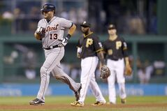 Detroit Tigers' Alex Avila (13) rounds the bases past Pittsburgh Pirates right fielder Josh Harrison, center, and shortstop Jordy Mercer after hitting a solo home run in the fourth inning of the baseball game on Tuesday, Aug. 12, 2014, in Pittsburgh. (AP Photo/Keith Srakocic)