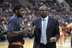 Cleveland Cavaliers head coach Mike Brown, right, talks to Kyrie Irving during a time out in the second half of an NBA basketball game against the Philadelphia 76ers on Tuesday, Feb. 18, 2014, in Philadelphia. The Cavaliers defeated the 76ers 114-85. (AP Photo/Michael Perez)