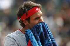 Switzerland's Roger Federer wipes his face during the first round match of the French Open tennis tournament against Slovakia's Lukas Lacko at the Roland Garros stadium, in Paris, France, Sunday, May 25, 2014. (AP Photo/Darko Vojinovic)