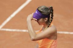 Switzerland's Belinda Bencic adjusts her cap during the first round match of the French Open tennis tournament against Venus Williams of the US at the Roland Garros stadium, in Paris, France, Sunday, May 25, 2014. Bencic lost in two sets 4-6, 1-6. (AP Photo/David Vincent)