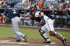 Arizona Diamondbacks' Miguel Montero, right, tags Milwaukee Brewers' Scooter Gennett (2) out after the third strike was dropped by Montero during the first inning of a baseball game on Monday, June 16, 2014, in Phoenix. (AP Photo/Ross D. Franklin)