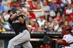 Miami Marlins' Casey McGehee, left, follows through after hitting a two-run double off Philadelphia Phillies starting pitcher Roberto Hernandez during the first inning of a baseball game, Monday, June 23, 2014, in Philadelphia. At right is catcher Carlos Ruiz. (AP Photo/Matt Slocum)