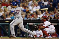 New York Mets' Juan Lagares, left, follows through after hitting an RBI-double off Philadelphia Phillies starting pitcher A.J. Burnett during the fourth inning of a baseball game, Friday, Aug. 8, 2014, in Philadelphia. Phillies catcher Carlos Ruiz, right, looks on. (AP Photo/Matt Slocum)