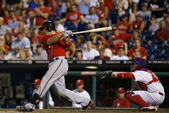 Washington Nationals' Ryan Zimmerman, left, follows through after hitting a go-ahead RBI-single off Philadelphia Phillies relief pitcher Jake Diekman during the 10th inning of a baseball game, Saturday, July 12, 2014, in Philadelphia. Washington won 5-3 in 10 innings. At right is catcher Koyie Hill. (AP Photo/Matt Slocum)