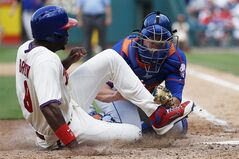 Philadelphia Phillies' Domonic Brown, left, is tagged out at home plate by New York Mets catcher Anthony Recker after trying to score on a single by Ben Revere during the seventh inning of a baseball game, Monday, Aug. 11, 2014, in Philadelphia. New York won 5-3. (AP Photo/Matt Slocum)