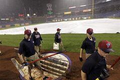 Grounds crew members cover the field during a rain delay in the sixth inning of a baseball game between the Philadelphia Phillies and the Washington Nationals, Saturday, May 3, 2014, in Philadelphia. (AP Photo/Laurence Kesterson)