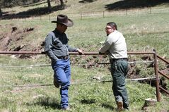 Otero cattle rancher association president Gary Stone talks to Lincoln National Forest District Ranger James Duran in Weed, New Mexico, Thursday, May 15, 2014. The Otero County Cattleman's Association is pitted against the National Forest Service over a fence intended to protect wildlife that the agency installed around a small creek where the ranchers' cattle drink water. (AP Photo/Juan Carlos Llorca)