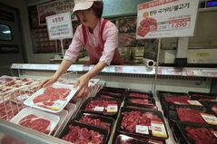 A South Korean store employee sets out packs of domestic beef on the shelves at a Lotte Mart store in Seoul, South Korea, Wednesday, April 25, 2012. Two major South Korean retailers, including Lotte Mart, suspended sales of U.S. beef Wednesday following the discovery of mad cow disease in a U.S. dairy cow. Reaction elsewhere in Asia was muted with Japan saying there's no reason to restrict imports. The letters on a card at left top read