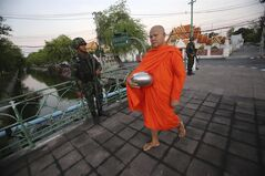 A Buddhist monk walks past soldiers in Bangkok, Thailand, Friday, May 23, 2014 after Thai military staged a coup. Thailand's new military junta has announced that it has suspended the country's constitution. Without firing a shot, Thailand's powerful military seized control of this volatile Southeast Asian nation Thursday, suspending the constitution and detaining Cabinet ministers in a risky bid to end half a year of political upheaval that many fear will only deepen the nation's crisis. (AP Photo/Sakchai Lalit)