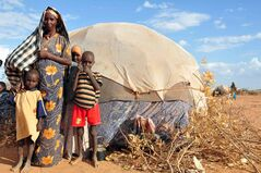 Osoba Hassan stands outside her makeshift home with three of her children at the Ifo camp in the Dadaab refugee complex in northeastern Kenya. Humankind International was created to help refugee children.