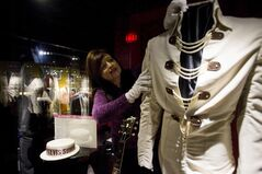 "Archivist Dee Dee Antle adjusts one of Elvis Presley's famous jumpsuits during the opening of Graceland's newest exhibition in Memphis, Tenn., March 4, 2013. ""Elvis: Live from Vegas."" The show features footage from some of"