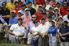 Phil Mickelson, lower left, watches along with the gallery as his chip shot sails to the green on the 16th hole during the final round of the St. Jude Classic golf tournament Sunday, June 8, 2014, in Memphis, Tenn. Mickelson made par on the hole and finished the tournament at 6-under 274. (AP Photo/Mark Humphrey)