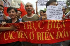 FILE - In this June 12, 2011 file photo, Vietnamese protesters carry a banner with a Vietnamese slogan reading,