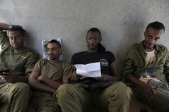 Israeli reserve soldiers rest in a shaded area near the Israel Gaza border on Thursday, Aug. 7, 2014. (AP Photo/Tsafrir Abayov)