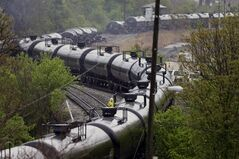 Firefighters and rescue workers work along the tracks where several CSX tanker cars carrying crude oil derailed and caught fire along the James river near downtown in Lynchburg, Va., Wednesday, April 30, 2014. Nearby buildings were evacuated for a time, but officials said there were no injuries and the city on its website and Twitter said firefighters on the scene made the decision to let the fire burn out. (AP Photo/Steve Helber)