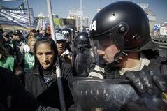 Riot police cordon off protesters partially blocking one of the main access roads to Buenos Aires over the Riachuelo River, in Argentina, Wednesday, Aug. 27, 2014. CTA, an opposition union umbrella group, started a 36-hour strike to demand more jobs, better salaries and tax cuts. (AP Photo/Victor R. Caivano)