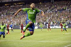 Seattle Sounders' Clint Dempsey leaps in the air after he scored a goal against the Portland Timbers, in the second half of an MLS soccer match, Sunday, July 13, 2014, in Seattle. The Sounders won 2-0. (AP Photo/Ted S. Warren)
