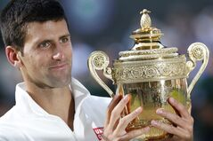 Novak Djokovic of Serbia holds the trophy after defeating Roger Federer of Switzerland in the men's singles final at the All England Lawn Tennis Championships in Wimbledon, London, Sunday July 6, 2014. (AP Photo/Ben Curtis)