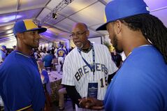 Cecil Cooper talks to Milwaukee Brewers' Khris Davis, left, and Rickie Weeks, right, during a Milwaukee Brewers Wall of Honor ceremony before a baseball game between the Milwaukee Brewers and the Cincinnati Reds Friday, June 13, 2014, in Milwaukee. (AP Photo/Morry Gash)
