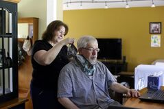 This photo taken May 8, 2014 shows Mark Matulaitis as his wife Colleen helps him with a neck brace that he wears after a recent operation, with his laptop that he uses for virtual house calls with his neurologist in his home in Salisbury, Md. Matulaitis has had Parkinson's disease since 2011 and sees a neurologist at the University of Rochester via his laptop and special Skype-like software. (AP Photo/Patrick Semansky)