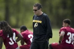 In this photo taken May 5, 2013, Washington Redskins owner Dan Snyder walks by players during a rookie minicamp practice session at Redskins Park in Ashburn, Va. In an exclusive interview with the Associated Press conducted Friday, Oct. 4, 2013, Obama said he would