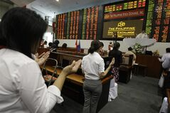 Filipino traders hear a mass before the start of the first day of trading at Philippine Stock Exchange at the financial district of Makati, south of Manila, Philippines on Wednesday Jan. 2, 2013. Stock markets in Asia registered relief Wednesday over the U.S. congressional vote to stop hundreds of billions of dollars in automatic tax increases and spending cuts that risked plunging the world's biggest economy into recession. (AP Photo/Aaron Favila)