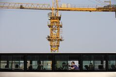 A man yawns in a bus which drives past a construction site in Beijing, China Tuesday, April 29, 2014. The International Monetary Fund raised its economic growth forecast for China on Monday but warned that its financial system faces risks due to the rapid expansion of debt. (AP Photo/Andy Wong)