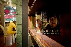 In this photo taken on Friday, Jan. 17, 2014, a girl has a drink near books shelf displaying Sherlock Holmes books at a