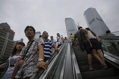People takes the escalators at the financial district Monday, Aug. 26, 2013 in Shanghai, China's financial hub. China's government says growth in the world's second-largest economy is showing signs of stabilizing after a lengthy decline. The chief spokesman for the Cabinet's statistics bureau, Sheng Laiyun, said Monday the government is confident it can meet its growth target of 7.5 percent this year. (AP Photo/Eugene Hoshiko)