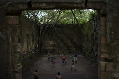 In this May 21, 2014 photo, Children and adults play soccer in the ruins of Paricatuba, near Manaus, Brazil. After the Italian migration dried up, the villa housed an art school run by French priests. The building's decline over the next century mirrored that of Manaus, which after the rubber boom went bust, slipped into a long period of decadence and decay. Then it became a penitentiary. Then a leper colony, before simply being abandoned to the tropical elements. (AP Photo/Felipe Dana)