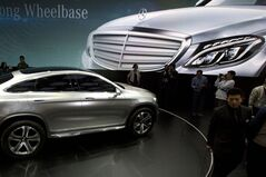 In this April 20, 2014 photo, visitors look at a Mercedes car at the company booth during the Auto China show in Beijing, China. Foreign companies in China feel increasingly targeted for unfair enforcement of anti-monopoly and other laws and might cut investment if conditions fail to improve, a business group said Tuesday, Sept. 2, 2014. (AP Photo/Ng Han Guan)