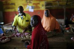 A Malian girl buys meat at the market in Gao, Northern Mali, Tuesday Jan. 29, 2013, days after Malian and French military forces closed in and retook the town from Islamist rebels. Earlier Tuesday, four suspected extremists were arrested after being found by a youth militia calling themselves the