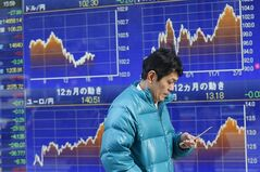 A man uses a mobile phone in front of a securities firm's electronic stock board in Tokyo, Monday, Feb. 24, 2014. Asian stock markets mostly fell Monday after a slower increase in Chinese property prices added to jitters about the strength of the world's No. 2 economy. Japan's Nikkei 225 stock average was down 0.19 percent at 14,837.68. (AP Photo/Shizuo Kambayashi)