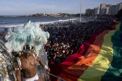 FILE - In this Oct. 13, 2013 file photo, a man in a carnival costume dances as people carry a rainbow gay pride flag during the annual gay pride parade on Copacabana beach in Rio de Janeiro, Brazil. Gay rights activists in Brazil are using the spotlight of the World Cup to draw attention to the harsh penalties gay people face in many of the countries represented at soccer's premier event. (AP Photo/Felipe Dana, File)