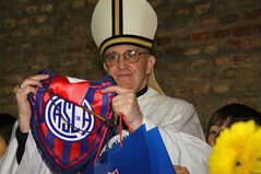 In this March 24, 2011 image released by the San Lorenzo de Almagro soccer team on March 13, 2013, Argentina's Cardinal Jorge Bergoglio holds up a small flag of the San Lorenzo soccer team in Buenos Aires, Argentina. Bergoglio, a San Lorenzo soccer fan, was chosen as Pope on March 13, 2013, the first pope ever from the Americas and the first from outside Europe in more than a millennium. (AP Photo/Club Atletico San Lorenzo de Almagro)