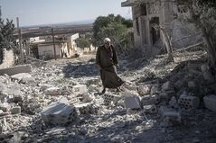 A Syrian man walks among rubble of destroyed residential buildings minutes after an airstrike hit Habit village, in the Syrian central province of Hama, Wednesday, Sep. 25, 2013. (AP Photo)