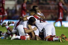 River Plate's players celebrate with teammate Gabriel Mercado, not seen, after he scored against Argentinos Juniors during an Argentine league soccer match in Buenos Aires, Argentina, Sunday, May 11, 2014. (AP Photo/Natacha Pisarenko)