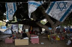 An Israeli homeless man sleeps on a sofa outside his tent where other homeless live for a couple of years, in a public park in the center of Tel Aviv, Israel, Tuesday, June 24, 2014. Israel on Tuesday joined an influential group of rich nations that help poor indebted economies, giving the country an international boost of recognition for its economic accomplishments. The news that Israel had been accepted into the Paris Club of creditor nations was welcomed by Israeli policy makers, who are facing calls to reduce high levels of poverty and inequality even as the country's economy appears to be humming along. (AP Photo/Oded Balilty)