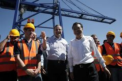 Greek Prime Minister Antonis Samaras, center left, shows the way to his Chinese counterpart Li Keqiang during their visit at the port of Piraeus, where Chinese shipping giant Cosco controls two of the three container terminals, on Friday June 20, 2014. Li is in Greece on a three day official visit during which both sides are expected to sign bilateral agreements. (AP Photo/Petros Giannakouris, Pool)