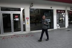 At the entrance of a closed Laiki Bank graffiti sprayed on the pavement reads in Greek