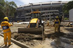 Workers remove mud after heavy rains outside Maracana stadium in Rio de Janeiro, Brazil, Wednesday, March 6, 2013. Concerns over preparations at the Maracana, ahead of the Confederations Cup, increased after FIFA and the local World Cup organizing committee were forced to cancel an inspection visit because the stadium was flooded. Parts of the construction site and some equipment were virtually submerged after the heavy rain that fell in Rio de Janeiro late Tuesday. (AP Photo/Silvia Izquierdo)