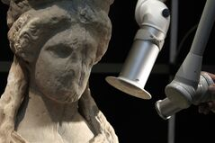 In this March 28, 2014 photo, a conservator uses a laser to clean a Caryatid at the Acropolis museum in Athens. It takes about seven months to clean each of the larger than life-sized statues, which were carved around 420 B.C. Work began in 2011, and is expected to be finished in June. (AP Photo/Thanassis Stavrakis)
