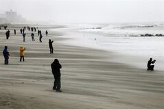 People brave high winds and blowing sand as they watch the rising surf at Coney Island Beach in the Brooklyn borough of New York as Hurricane Sandy arrives, Monday, Oct. 29, 2012. Hurricane Sandy continued on its path Monday, as the storm forced the shutdown of mass transit, schools and financial markets, sending coastal residents fleeing, and threatening a dangerous mix of high winds and soaking rain. (AP Photo/Mark Lennihan)