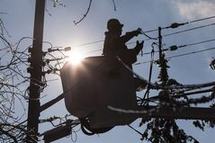A Toronto Hydro line worker works to restore power to a house in a Scarborough neighbourhood on Friday, December 27, 2013. THE CANADIAN PRESS/Chris Young