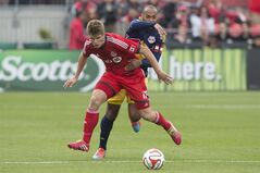 Toronto FC's Nick Hagglund, left, tussles with New York Red Bulls' Thierry Henry during first half MLS soccer action in Toronto on Saturday, May 17, 2014. THE CANADIAN PRESS/Chris Young