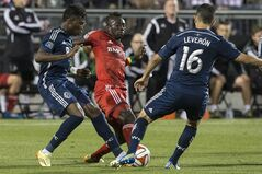 Toronto FC's Dominic Oduro (centre) battles for the ball with Vancouver Whitecaps' Sam Adekugbe (left) and Johhny Leveron during second half MLS action in Toronto on Wednesday July 16, 2014. THE CANADIAN PRESS/Chris Young