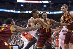 Toronto Raptors' DeMar DeRozan (centre) drives past Cleveland Cavaliers' Kyrie Irving (left) Tristan Thompson (centre right) and Tyler Zeller to score during first half NBA basketball action in Toronto on Friday February 21, 2014. THE CANADIAN PRESS/Chris Young