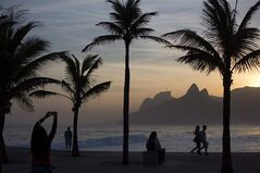 This Sept. 7, 2012 photo shows the sunset at Arpoador beach in Rio de Janeiro, Brazil. The Bank of Montreal (TSX:BMO) says a strong loonie and a relatively stable economy is fuelling a desire by many Canadians to get away over the Christmas-New Year's period. THE CANADIAN PRESS/AP/Felipe Dana